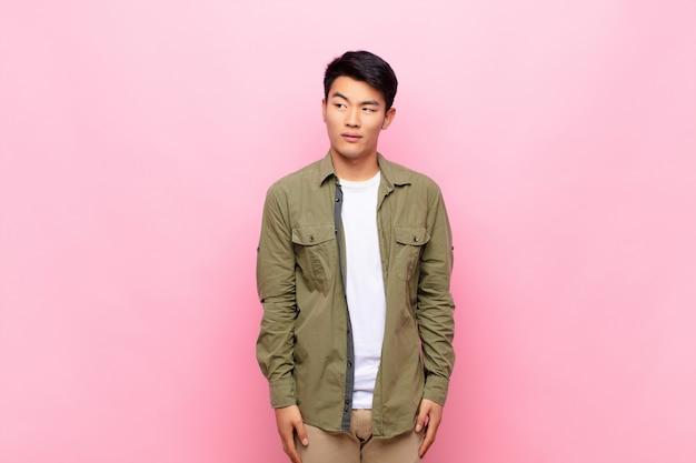 Jonge chinese man die bezorgd, gestrest, angstig en bang kijkt, in paniek raakt en tanden op elkaar klemt op een egale kleurenmuur