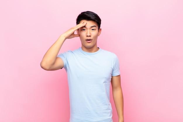 Jonge chinese man die er blij, verbaasd en verrast uitzag, glimlachte en verbazingwekkend en ongelooflijk goed nieuws realiseerde op een egale kleurenmuur