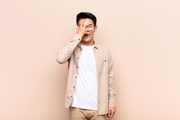 Jonge chinese man die geschokt, bang of doodsbang kijkt, kegelvormig gezicht met hand en gluren tussen vingers op egale kleurenmuur