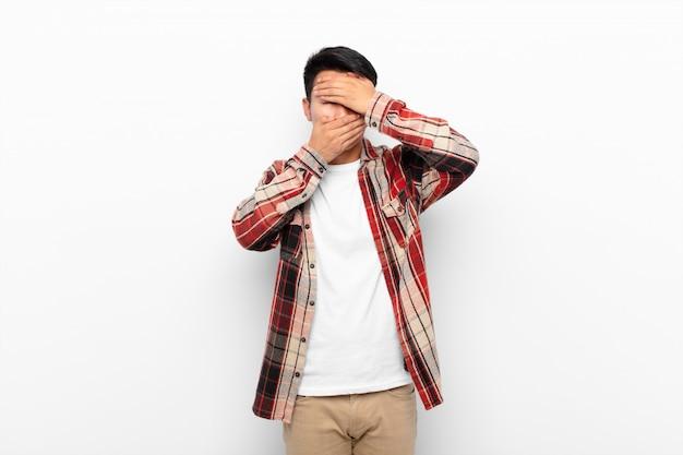 Jonge chinese man die gezicht bedekt met beide handen nee zeggen! afbeeldingen weigeren of foto's verbieden tegen een egale kleurenmuur