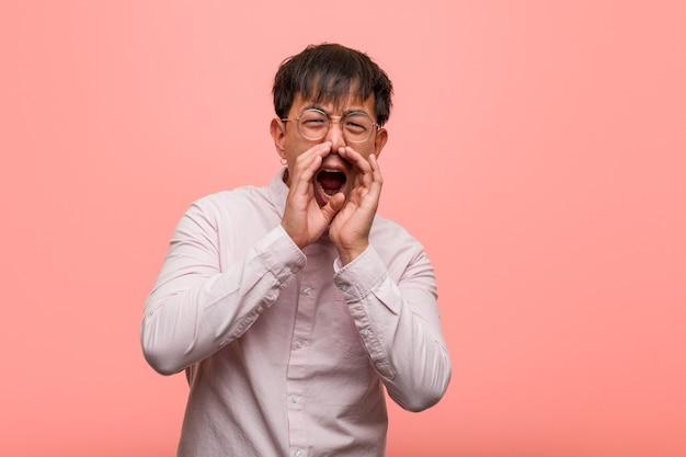 Jonge chinese man die iets blij naar voren schreeuwt