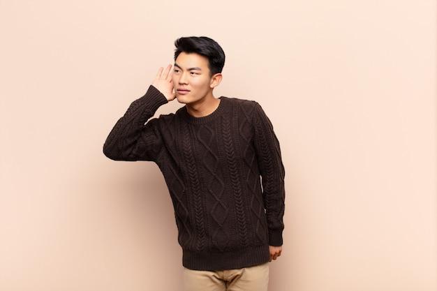 Jonge chinese man die lacht, nieuwsgierig naar de zijkant kijkt, probeert te luisteren naar roddels of een geheim hoort op een egale kleurenmuur