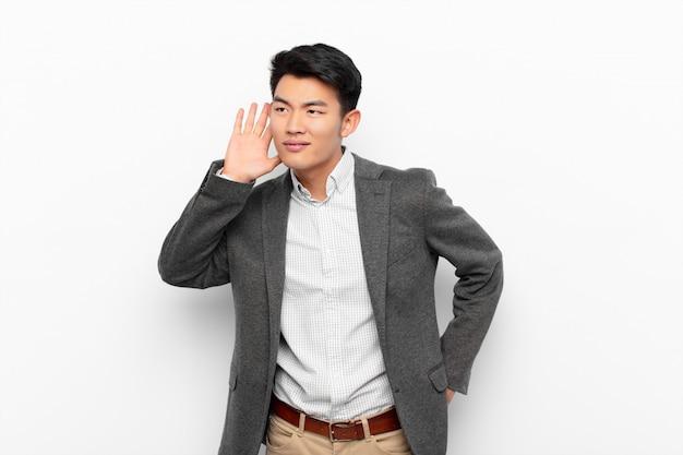 Jonge chinese man die lacht, nieuwsgierig opzij kijkt, probeert te luisteren naar roddel of een geheim afluistert tegen een egale kleurenmuur