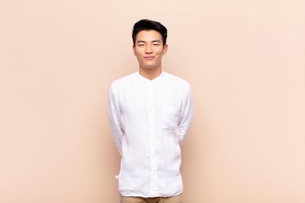 Jonge chinese man die positief en zelfverzekerd glimlacht, tevreden, vriendelijk en gelukkig kijkt op een egale kleurenmuur