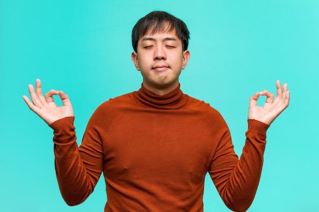 Jonge chinese man die yoga uitvoert