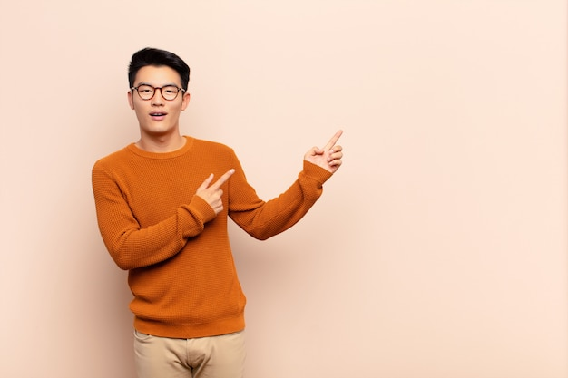 Jonge chinese man die zich blij en verrast voelt, lachend met een geschokte uitdrukking en naar de zijkant wijst op een egale kleurenmuur