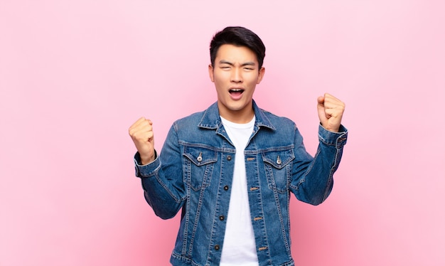 Jonge chinese man die zich gelukkig, positief en succesvol voelt, overwinning, prestaties of veel geluk viert op een egale kleurenmuur