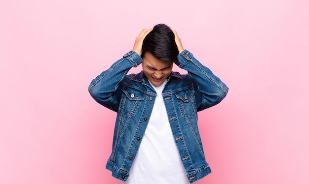 Jonge chinese man die zich gestrest en gefrustreerd voelt, handen opheft, zich moe, ongelukkig en met migraine tegen een effen kleurmuur voelt
