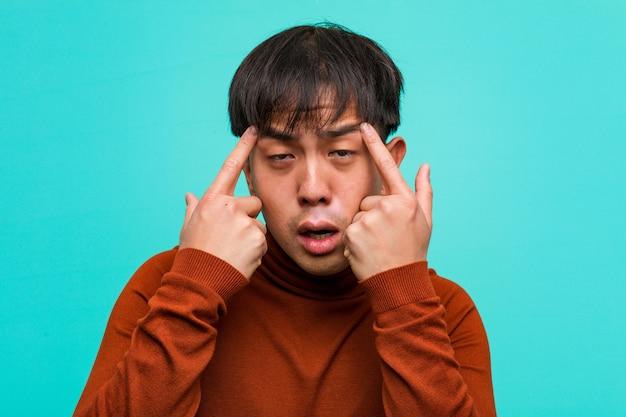 Jonge chinese man doet een concentratie gebaar
