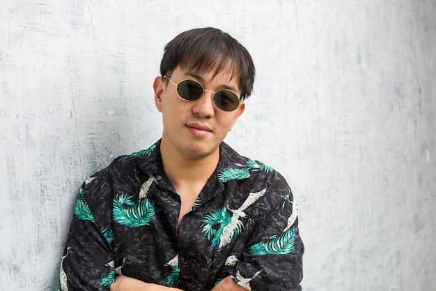 Jonge chinese man dragen zomer outfit kruising armen, glimlachend en ontspannen