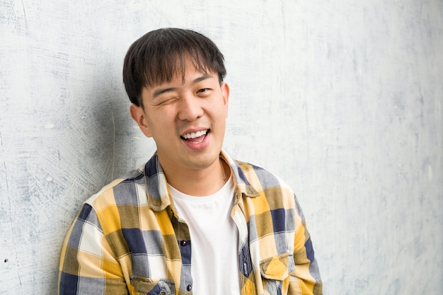 Jonge chinese man gezicht close-up knipogen, grappig, vriendelijk en zorgeloos gebaar