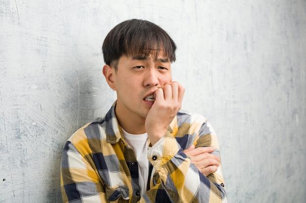 Jonge chinese man gezicht close-up nagels bijten, nerveus en erg angstig