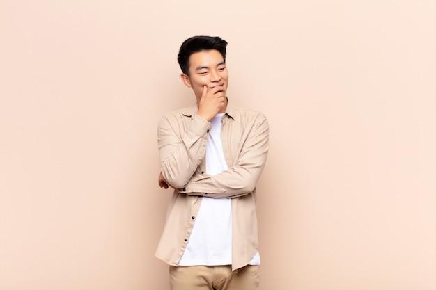 Jonge chinese man glimlachend met een gelukkige, zelfverzekerde uitdrukking met de hand op de kin, zich afvragend en naar de zijkant kijkend op een egale kleurenmuur