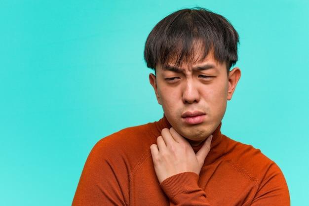 Jonge chinese man hoesten, ziek vanwege een virus of infectie
