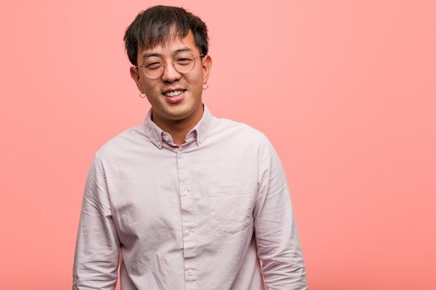 Jonge chinese man knipogen, grappig, vriendelijk en zorgeloos gebaar
