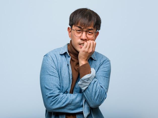 Jonge chinese man nagels bijten, nerveus en erg angstig
