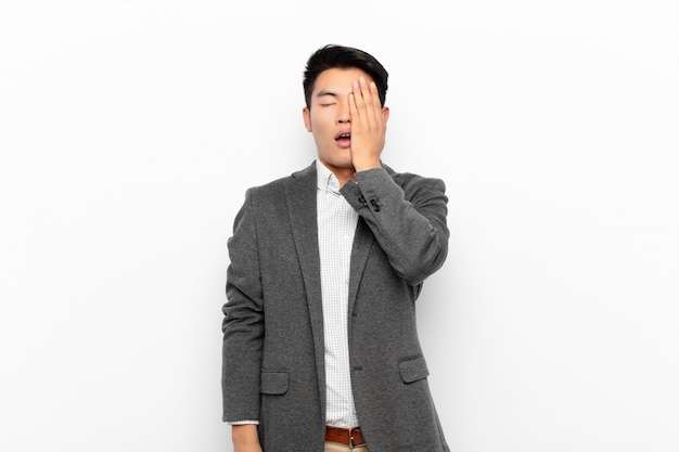 Jonge chinese man op zoek slaperig, verveeld en geeuwen, met hoofdpijn en een hand die de helft van het gezicht tegen een egale kleur muur