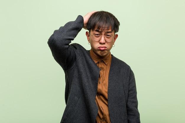 Jonge chinese man tegen een groene muur