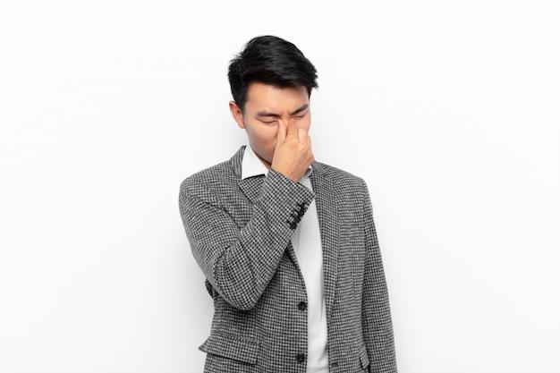 Jonge chinese man voelt zich gestrest, ongelukkig en gefrustreerd, raakt het voorhoofd aan en lijdt aan migraine van ernstige hoofdpijn tegen een egale kleurmuur
