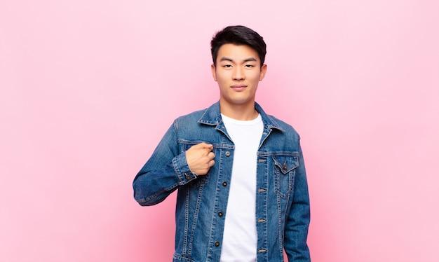 Jonge chinese man voelt zich verward, verbaasd en onzeker, wijst naar zichzelf en vraagt zich af wie, mij? tegen vlakke kleurenmuur