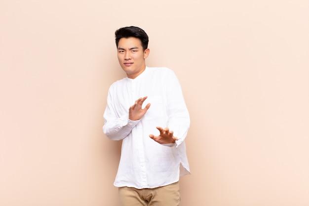 Jonge chinese man voelt zich walgelijk en misselijk en trekt zich terug van iets smerigs, stinkends of stinkends, en zegt gooi tegen kleurenmuur