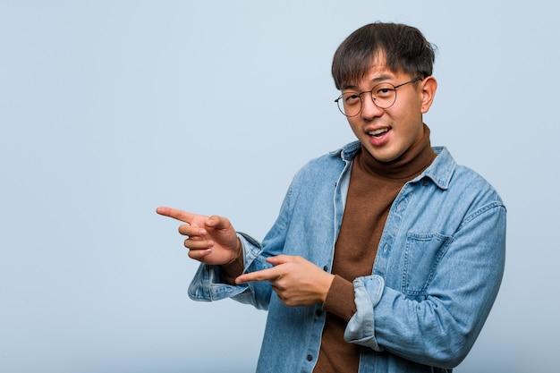 Jonge chinese man wijst naar de kant met vinger