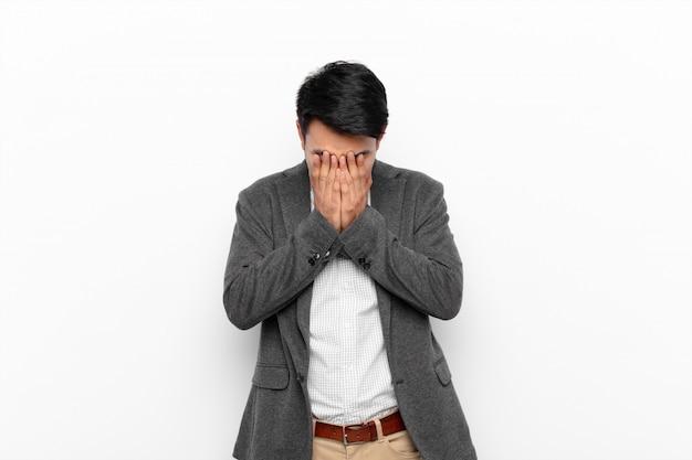 Jonge chinese mens die droevig, gefrustreerd, zenuwachtig en gedeprimeerd voelt, gezicht bedekkend met beide handen, schreeuwend tegen vlakke kleurenmuur