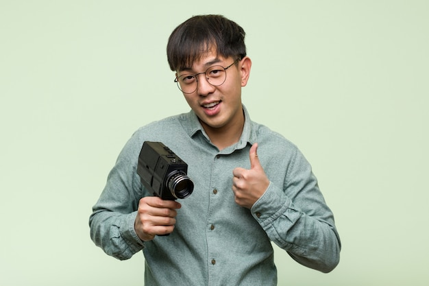 Jonge chinese mens die een uitstekende camera houdt glimlachend en duim opheffend