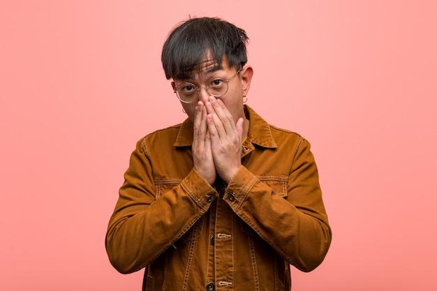 Jonge chinese mens die een verrast en geschokt jasje draagt
