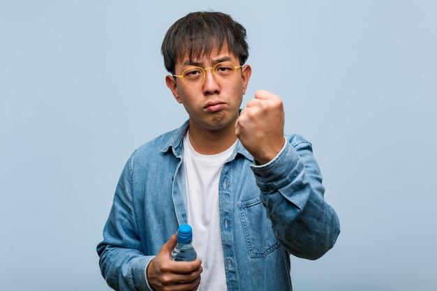 Jonge chinese mens die een waterfles houdt die vuist toont aan voorzijde, boze uitdrukking
