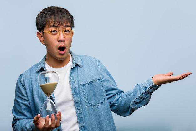 Jonge chinese mens die een zandloper houdt die iets op palmhand houdt