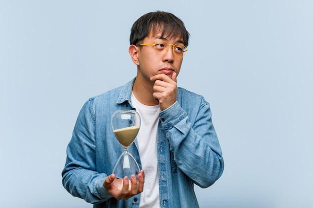 Jonge chinese mens die een zandtimer houdt die twijfelt en verwart