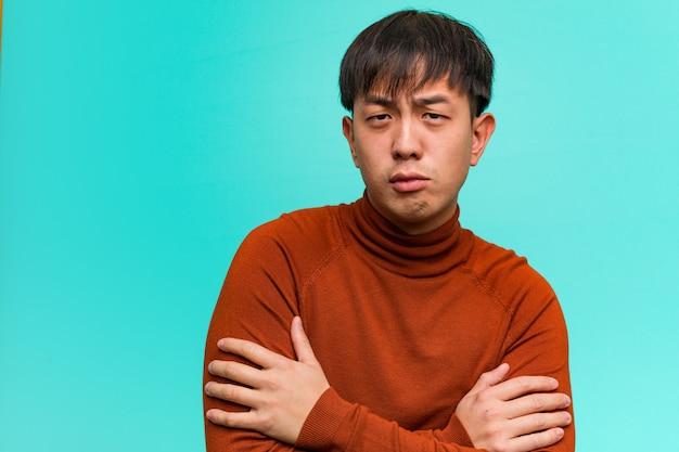 Jonge chinese mens die ontspannen wapens kruist