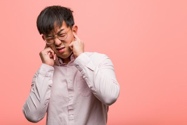 Jonge chinese mens die oren behandelt met handen