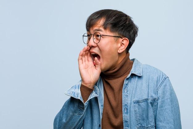 Jonge chinese mens die roddel ondertoon fluisteren