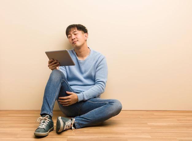 Jonge chinese mensenzitting die zijn tablet gebruiken die dromen van het bereiken van doelstellingen en doeleinden