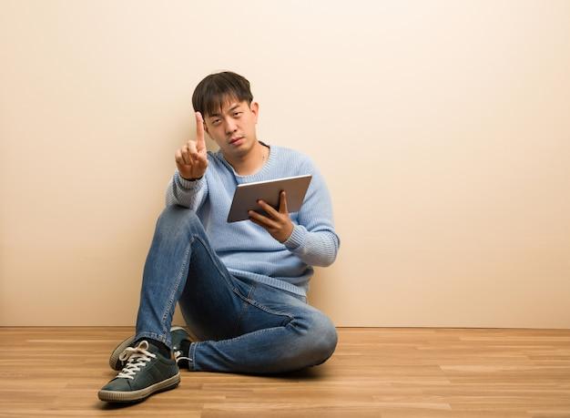 Jonge chinese mensenzitting die zijn tablet gebruiken die nummer één tonen