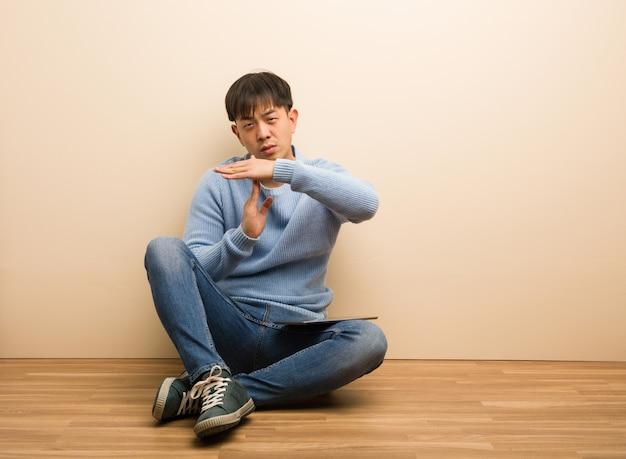 Jonge chinese mensenzitting die zijn tablet gebruikt die een time-outgebaar doet