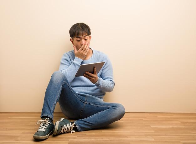 Jonge chinese mensenzitting die zijn tablet verrast en geschokt gebruikt