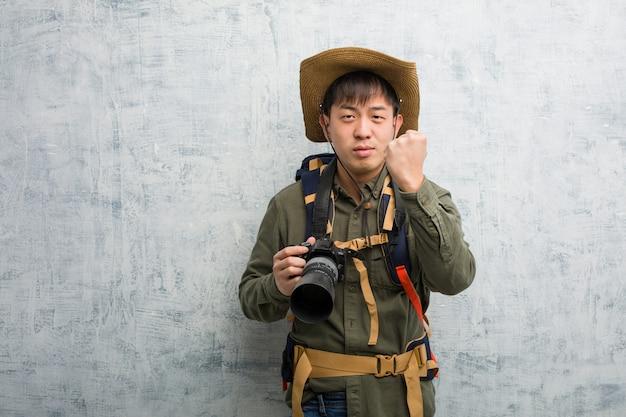Jonge chinese ontdekkingsreizigermens die een camera houden die vuist tonen aan voorzijde