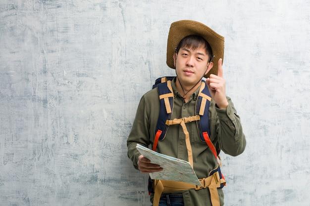 Jonge chinese ontdekkingsreizigermens die een kaart houden die nummer toont