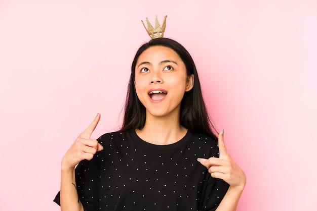 Jonge chinese prinsesvrouw die op een roze muur wordt geïsoleerd die oren met handen behandelt.