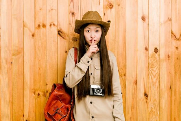 Jonge chinese reizigersvrouw die een geheim houdt of om stilte vraagt.