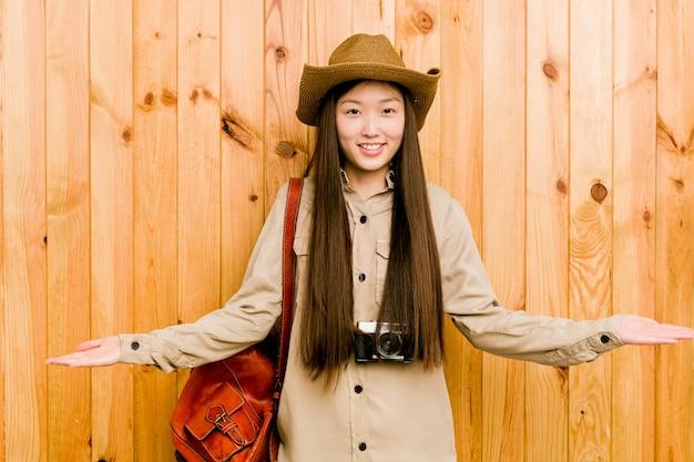 Jonge chinese reizigersvrouw die een welkome uitdrukking toont.