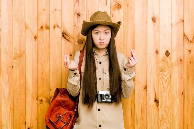 Jonge chinese reizigersvrouw die laat zien dat ze geen geld heeft.