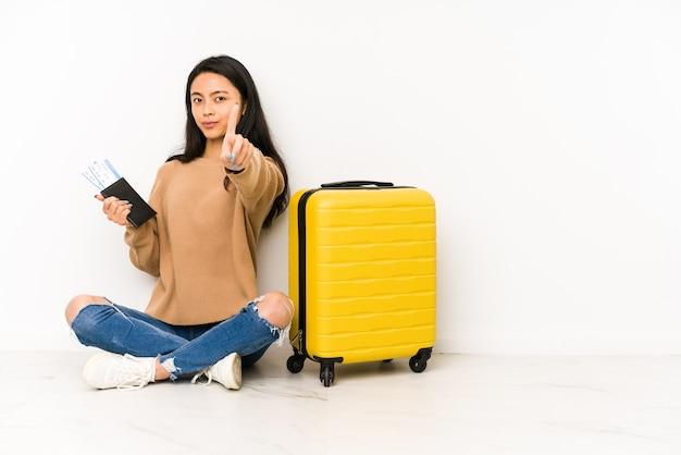 Jonge chinese reizigersvrouw die op de vloer met een geïsoleerde koffer zit die nummer één met vinger toont.