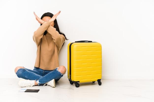 Jonge chinese reizigersvrouw die op de vloer met een geïsoleerde koffer zit die twee wapens gekruist houdt, ontkenningsconcept.