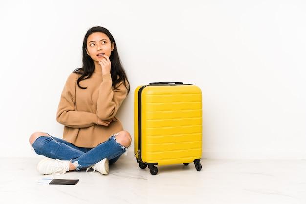 Jonge chinese reizigersvrouw die op de vloer met een geïsoleerde koffer zit, ontspannen na te denken over iets dat naar een exemplaarruimte kijkt.