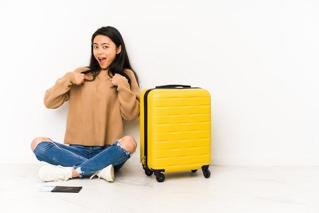 Jonge chinese reizigersvrouw die op de vloer met een geïsoleerde koffer zit, verrast wijzend met vinger, breed glimlachend.