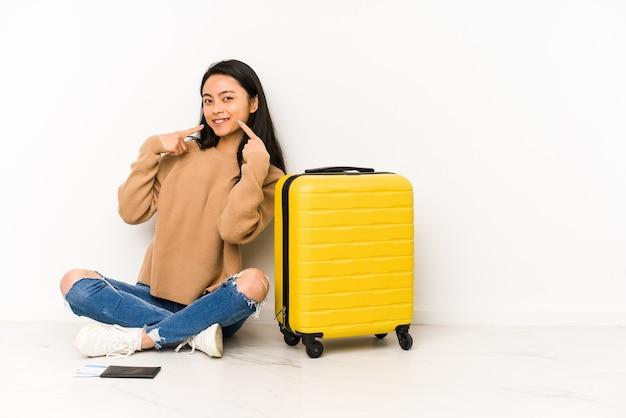 Jonge chinese reizigersvrouw die op de vloer zit met een geïsoleerde koffer glimlacht, wijzende vingers naar mond.